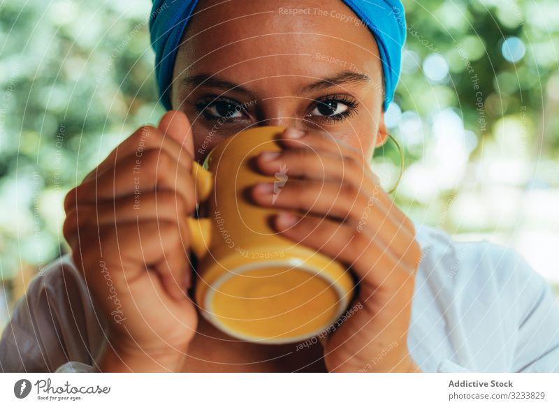 Woman in turban drinking coffee woman rest patio pleased smile content enjoy gaze tree head wrap rural costa rica greenery happy young terrace cup relax