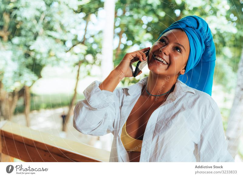 Woman with turban speaking on mobile phone woman positive smile smartphone using head wrap tanned attractive colorful greenery young happy fun photo costa rica