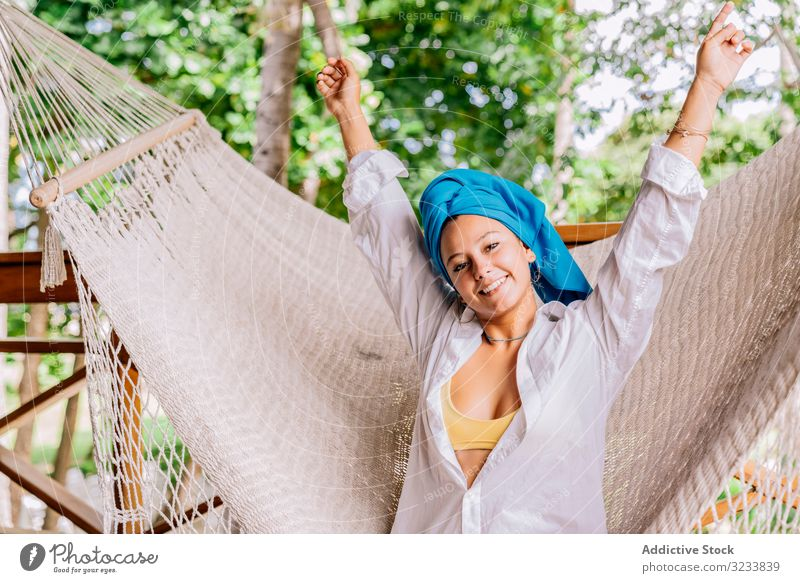 Pleased woman in turban resting in hammock on terrace happy smile raising hands sit tree greenery shirt peaceful costa rica young relax summer comfortable