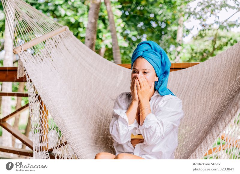 Woman in turban resting in hammock woman happy smile touching face sit terrace tree greenery shirt peaceful costa rica young relax summer comfortable lifestyle