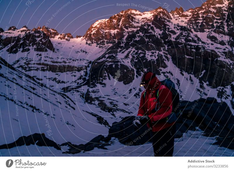 Mountaineer with flashlight standing at mountain cliff mountaineer rest bright jacket backpack snowy morocco toubkal africa picturesque peak twilight evening