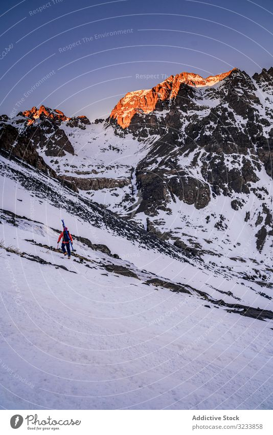 Tourist gazing at breathtaking snowy mountain slope tourist hiking backpack equipment contemplating africa morocco toubkal stand rocky colorful jacket person