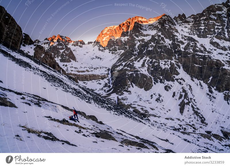 Tourists gazing at breathtaking snowy mountain slope tourist hiking backpack equipment contemplating africa morocco toubkal stand rocky colorful jacket person