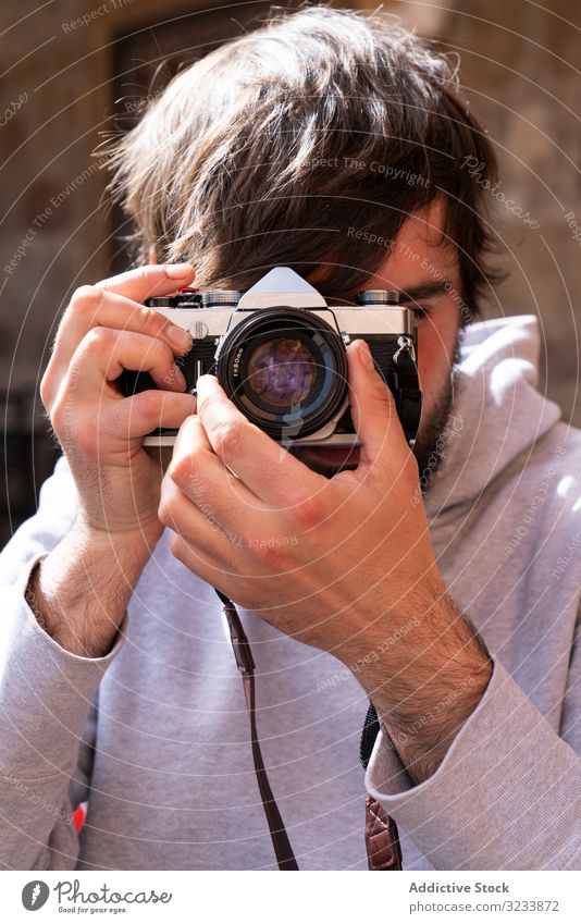 Male photographer taking picture with camera on street man positive casual adjusting using optics young adult photography professional creative lifestyle