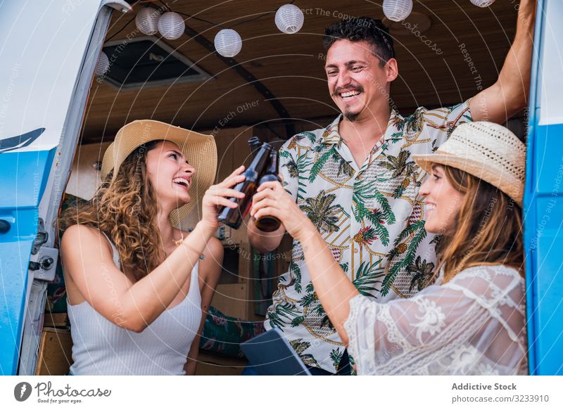 Smiling friends clinking bottles of beer celebrating vacation drinking car minivan women travel alcohol beverage party road showing together friendship
