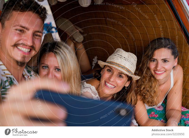 Smiling man taking selfie with girlfriends comfortable placing on trunk of blue car people smartphone seaside using music travel minivan having fun gadget