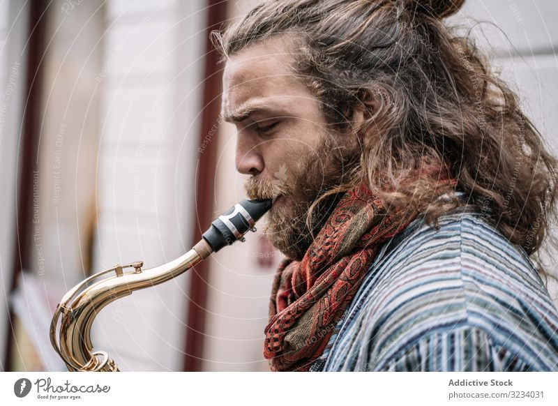 Male saxophonist plays Sax in the street artist blow pose sound adult music rock fun young musician male rocker man profile expressive guy handsome song active