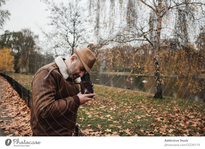 Male photographer standing in autumn park man photo camera retro london casual peaceful adult male great britain england vintage leaf fall season tree shoot