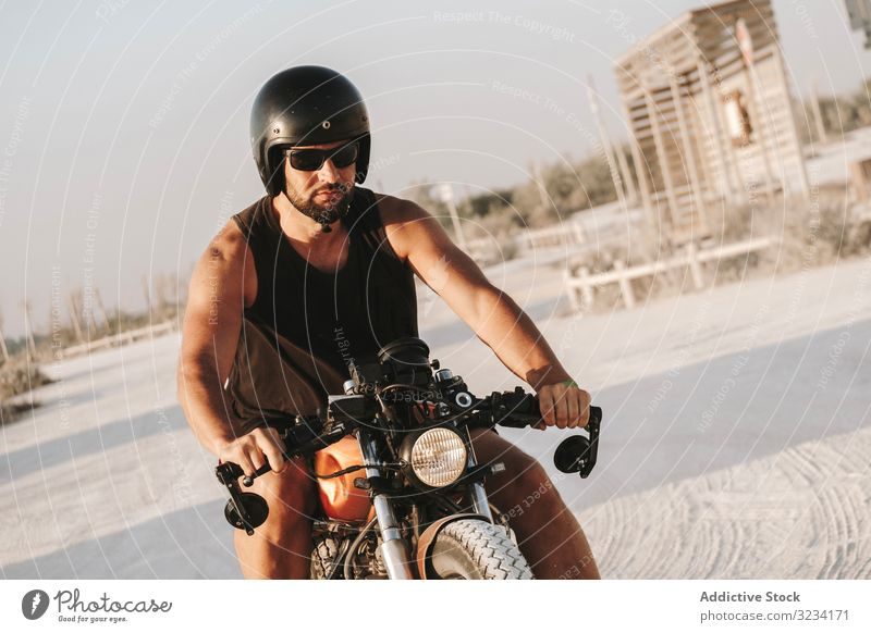 Strong man driving motorcycle drive road sunglasses serious strong male beard ride deserted transport bike biker freedom travel engine power transportation