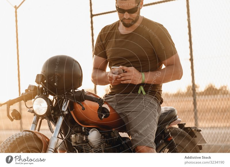 Man sitting on motorcycle and surfing mobile man smartphone rest using sunglasses focused wistful male field transport road bike biker break device gadget