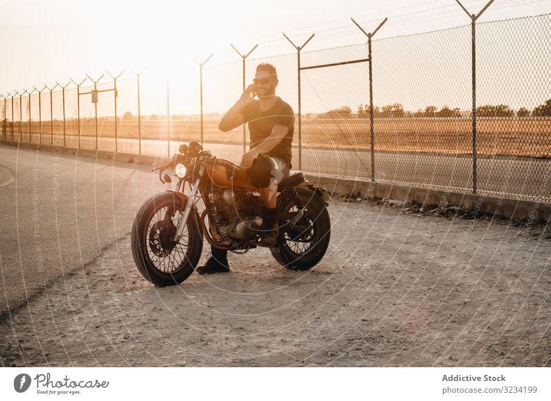 Man sitting on motorcycle and surfing mobile man smartphone rest using talking sunglasses focused wistful male field transport road bike biker break device