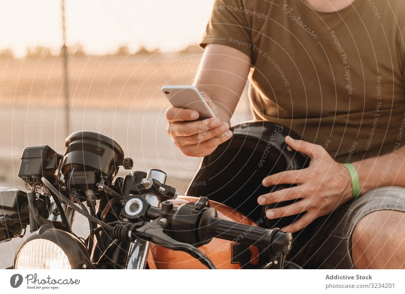 Man sitting on motorcycle and surfing mobile man smartphone rest using sunglasses focused wistful male field transport road bike biker device gadget watching