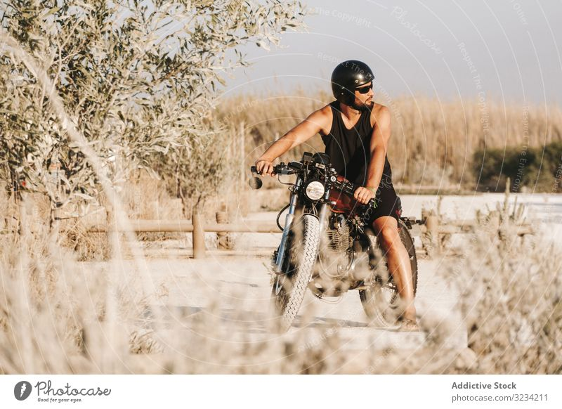 Serious male driving motorcycle in forest man helmet drive sunglasses brutal serious bold break field transport road bike biker freedom travel ride engine power