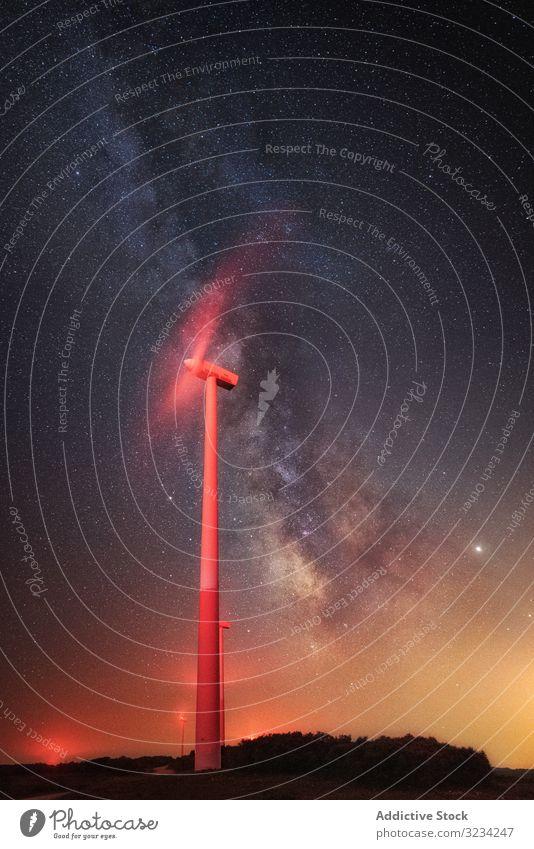 Illuminated wind turbine over starry night sky illuminated working generator milky way breathtaking landscape sustainable mill innovative technology electricity