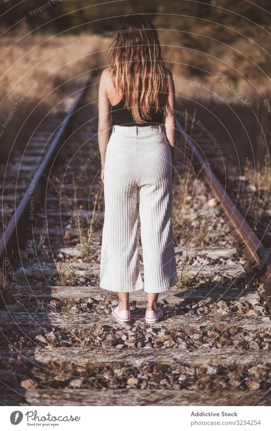 Long haired woman standing on railways overgrown with dry grass road travel nostalgia journey track railroad female classic passenger tourism destination