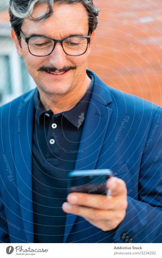 Senior businessman in blue jacket using smartphone browsing surfing mobile social media watching texting messaging adult aged senior communication internet