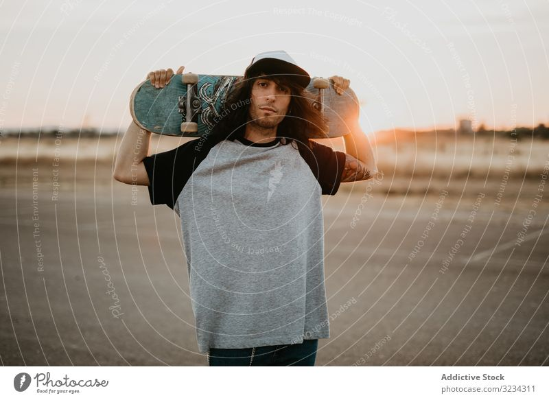 Cool confident teenager with skateboard looking at camera hipster cool man style millennial rural country street style cap generation sunset modern trendy