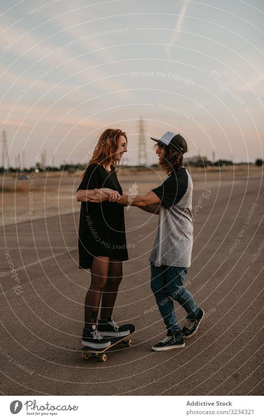 Teenage boy helping girlfriend to skate on road teenage skateboard learn couple together fun practice happy support cheerful urban cool modern generation ride