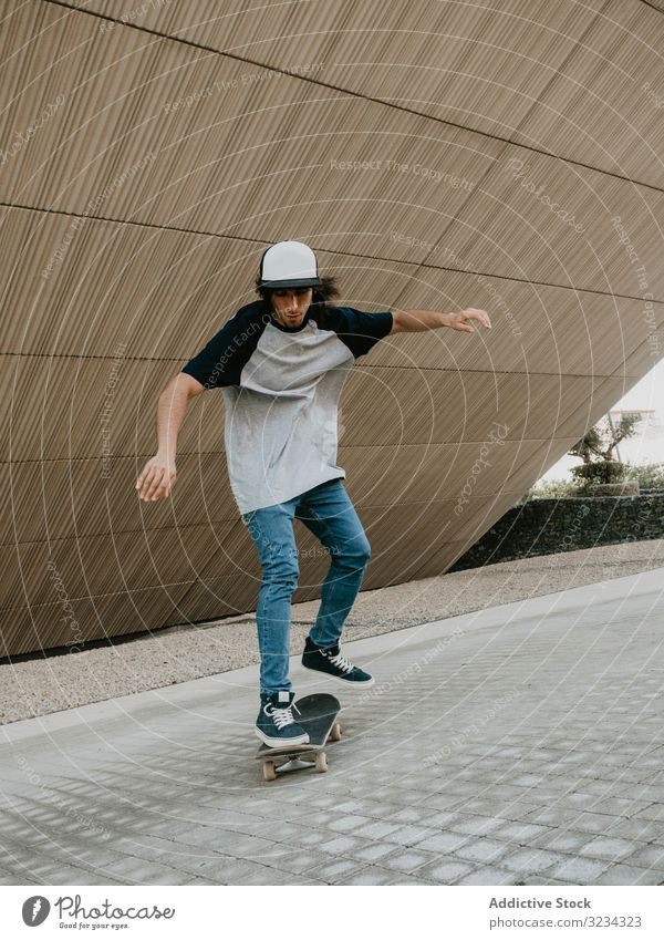 Sportive teenager riding skate on road along sloping wall man ride skateboard cool urban modern balance skater active exterior skateboarder practice freedom