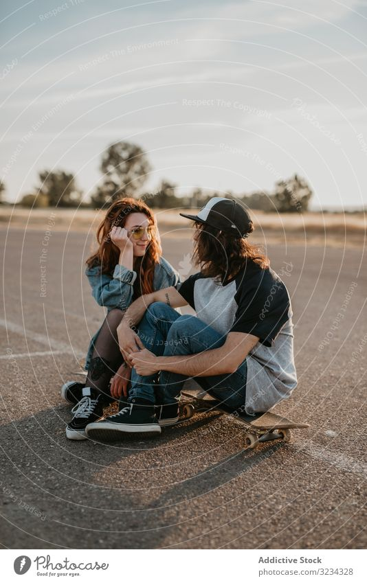 Skaters sitting on empty rural road chatting in sunlight couple teen skater together generation sport countryside hipster asphalt in love fun active modern