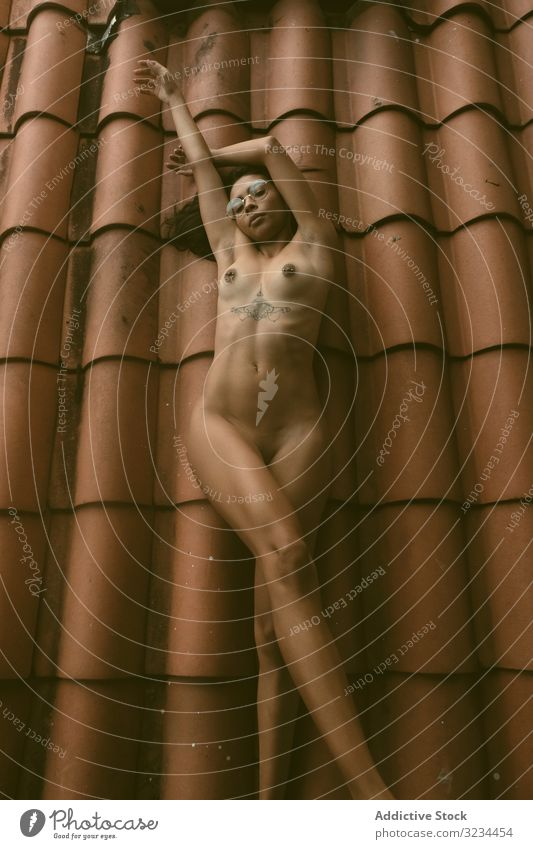 Naked woman lying on roof naked sensual raised arms ethnic tiled house young allure body rest female relax breast brunette lady hands up sexy tattoo call