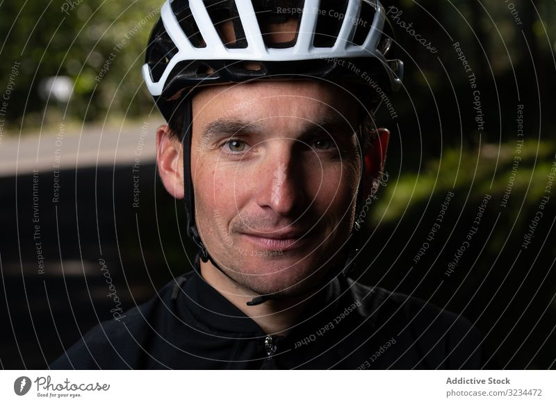 Positive cyclist looking at camera in park training positive man smile helmet sunny daytime sport summer male safety protection glad pleased adult uniform