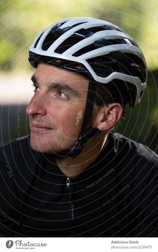 Positive cyclist looking away in park training positive man smile helmet sunny daytime sport summer male safety protection glad pleased adult uniform sportswear