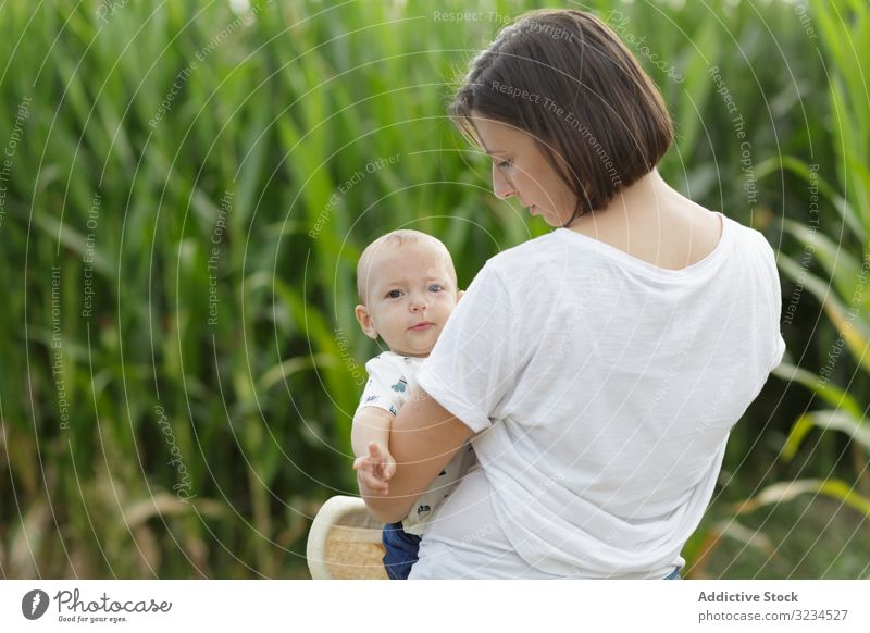 Adorable mother and child on hand enjoying and laughing in field family orchard parent happy fun together kid childhood little day cheerful motherhood joyful