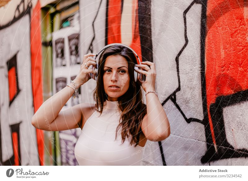 Woman listening to music and using smartphone woman headphones summer graffiti concrete street urban street style grunge social media smile happy gadget