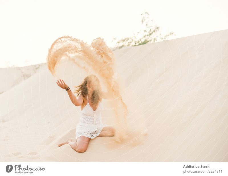 Woman having fun throwing sand in desert woman dune summer tropical vacation adult beautiful relax travel holiday playful recreation activity freedom active