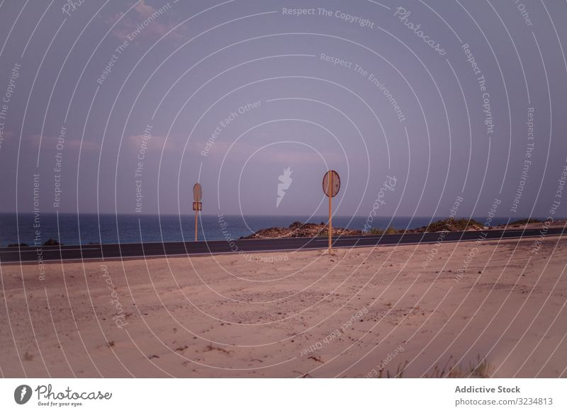 Warning signs on road along dry field and ocean seaside empty water beach warning summer tropical travel holiday motion recreation freedom emergency relaxation