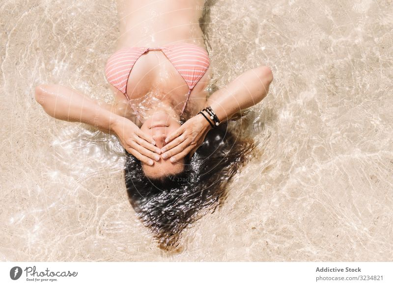 Woman in swimsuit lying in water on seashore woman seaside swimming summer beach leisure beautiful vacation swimwear coast floating cheerful holiday relaxation