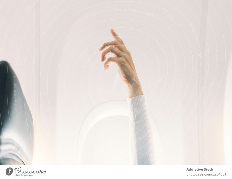 Person in white sweater raising hand up in plane light salon fly attention aircraft expression travel adult concept calm relaxed sitting question communication