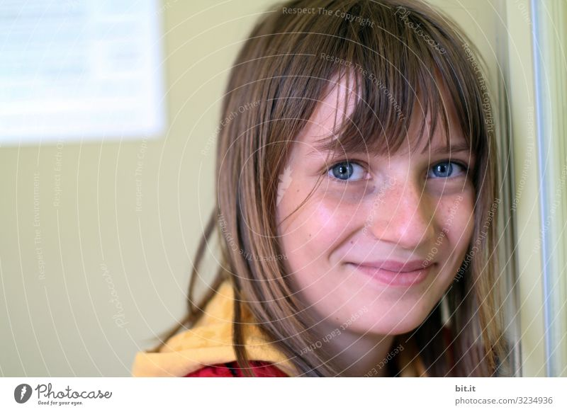 happy, happy girl with bangs and blue eyes, leaning against a wall of a building, and naturally looking into the camera with a smile. Education School Study