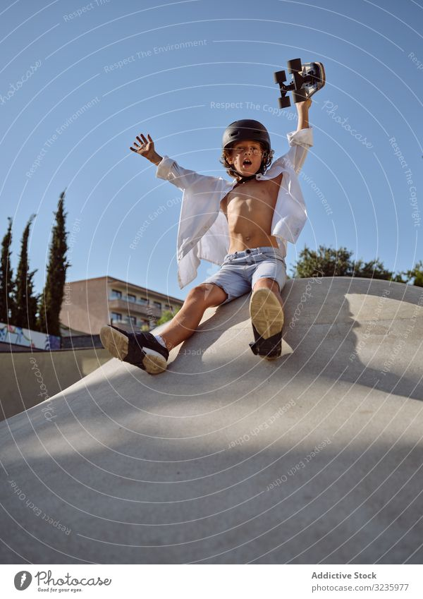 Child on ramp with skateboard in hand child skatepark ride fun helmet trick modern blue sky yell sport leisure hobby ready boy young carefree childhood summer