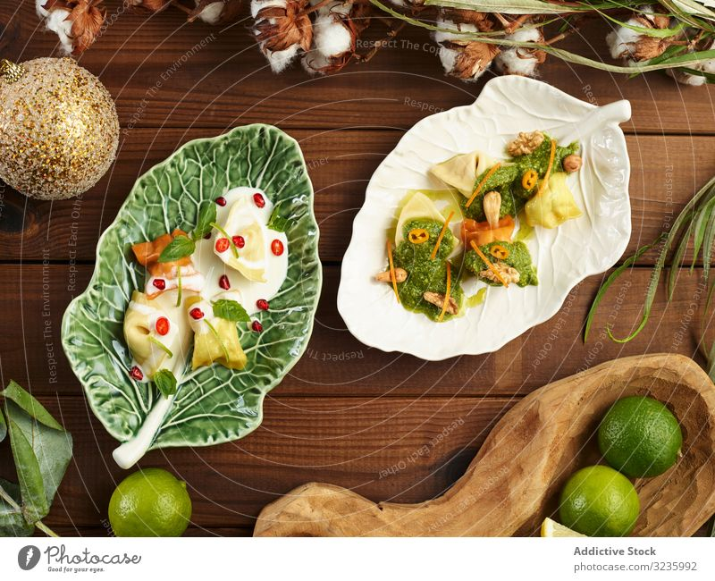 Ceramic leaf with yummy ravioli and sauce plate nut served table artisan fresh pasta meal food dumplings dinner italian lunch portion traditional gourmet