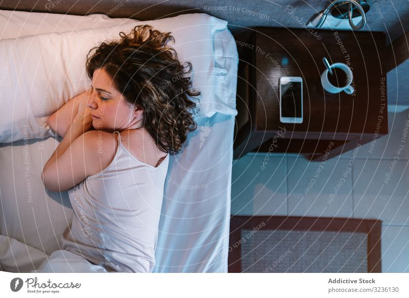Woman dozing in bed after breakfast morning woman sleep home rest calm drink device smartphone hotel relax bedroom vacation holiday closed eyes day off sleeping
