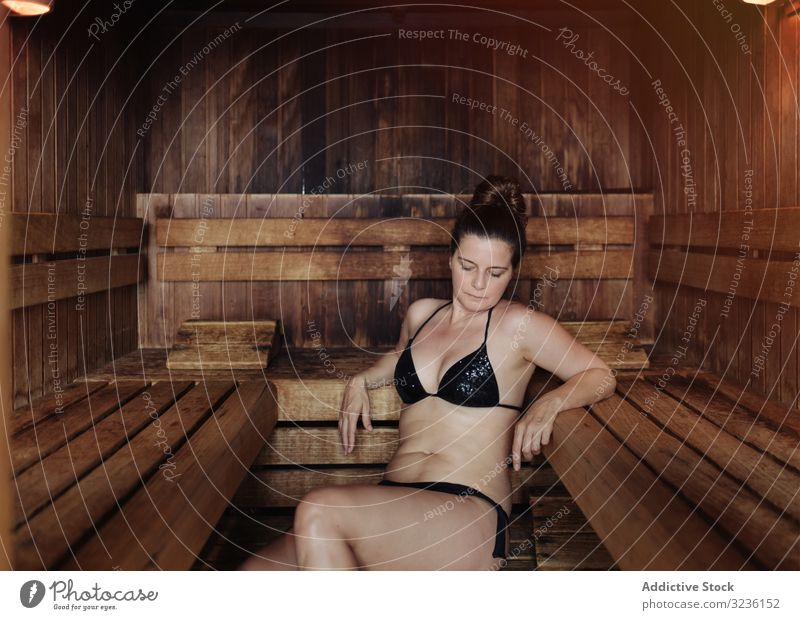 Adult female relaxing in sauna woman relaxation spa wellness steam room center therapy heat bikini attractive imperfect brunette calm adult health body care