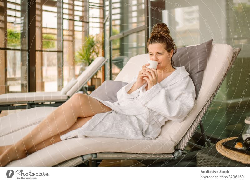 Content female relaxing in wellness center woman spa enjoyment bathrobe chaise lounge drink rest content positive comfortable pensive thoughtful natural