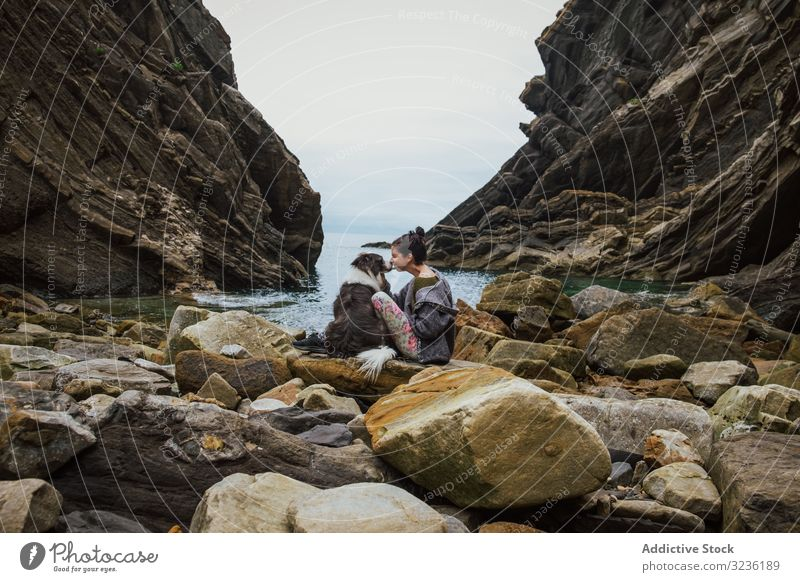 Traveling woman kissing dog sitting on boulder coast travel tourism friend border collie love bay loyalty shore happy doggy gorge tranquil environment horizon