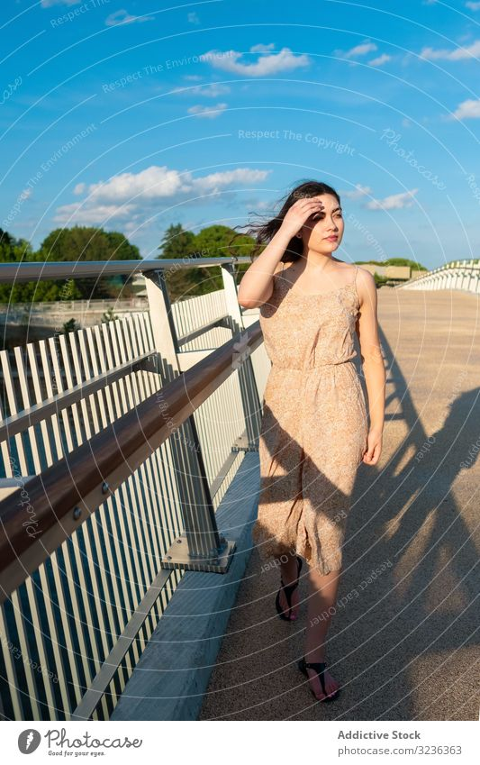 Peaceful woman in dress walking along rural bridge peaceful relaxed dreamy sundress sunny wind stroll blue sky touching face young adult countryside happy