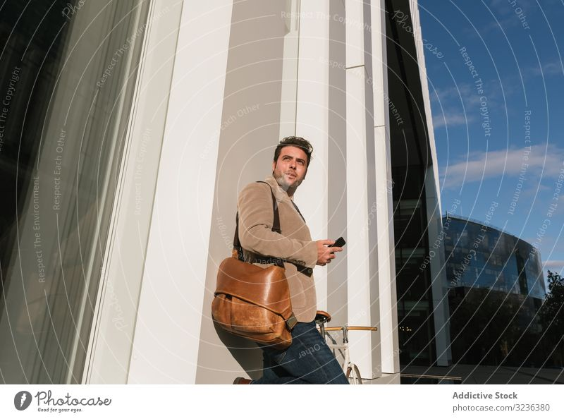 Businessman with smartphone leaning on building on city street businessman wall downtown male professional entrepreneur device gadget using browsing success job