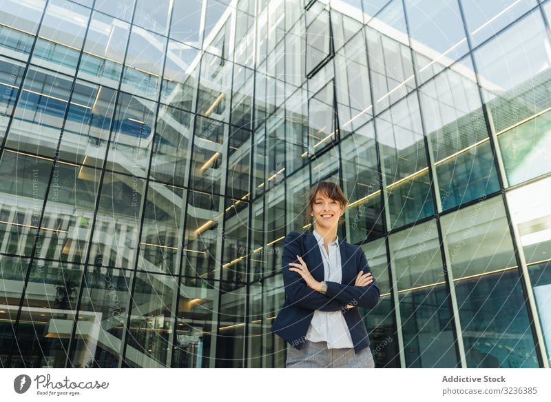 Confident businesswoman outside modern building confident street city smile crossed arms adult female elegant casual folded positive urban town contemporary