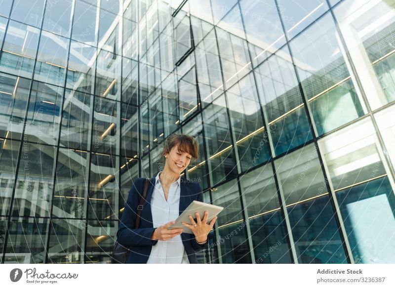 Positive businesswoman using tablet on street city positive modern smile adult building female elegant casual confident urban town contemporary work glass wall