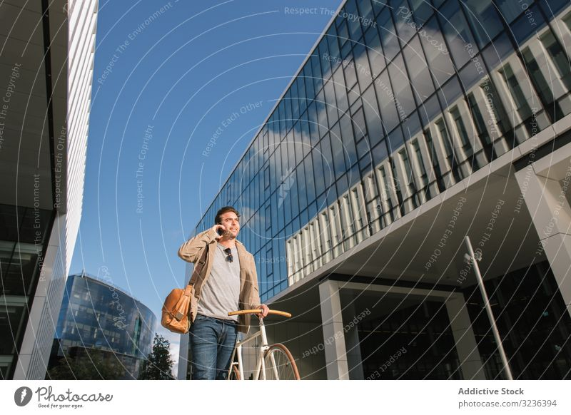 Man phoning while standing against modern building in downtown smartphone man mobile phone street skyscraper urban talk bike pensive delivery share conversation