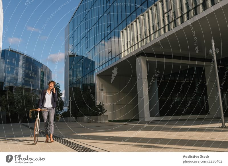Cheerful manager with bicycle talking on smartphone businesswoman street city walk positive modern smile adult building female elegant casual confident urban