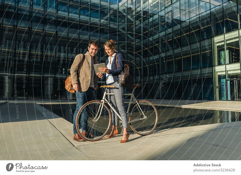 Businesspeople talking on street after work businesspeople smile building bicycle man woman colleague together couple office casual city town urban modern