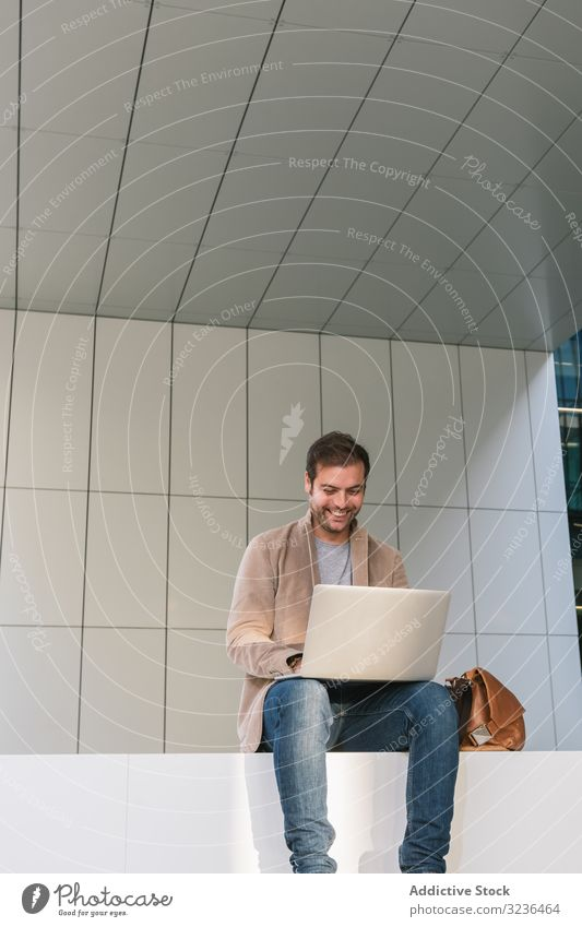 Cheerful businessman using laptop on street city smile sit building downtown male adult casual professional entrepreneur device gadget browsing job smart
