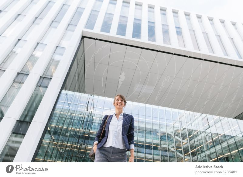 Happy female manager walking from work businesswoman street city positive modern smile adult building elegant casual confident urban town contemporary glass