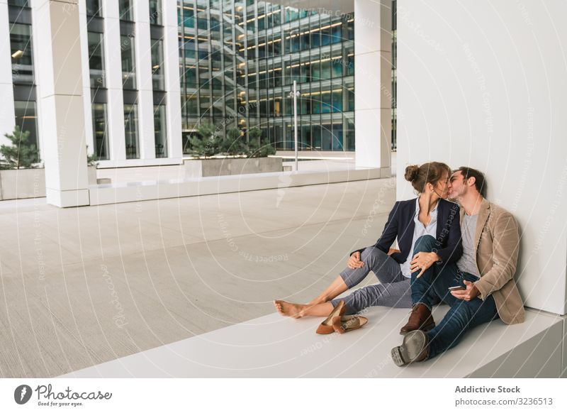 Businesspeople hugging and using smartphone on street businesspeople couple social media building sit rest city together man woman manager entrepreneur casual